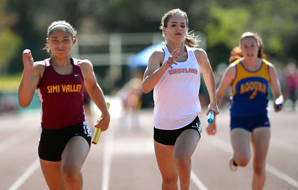 . Simi Valley High School\'s Kolbie Mabry and Noelle Schiller of Westlake compete in the 4X100 relay during the Marmonte League track and field finals May 9, 2014 in Moorpark.(Andy Holzman/Los Angeles Daily News)