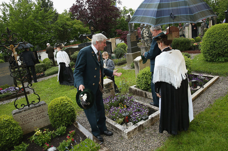 . Participants wearing traditional Bavarian folk costumes visit the local cemetery under drizzling rain after attending the annual Corpus Christi (in German called Fronleichnam) mass at St. Michael\'s Church on May 30, 2013 in Seehausen am Staffelsee, Germany. The Seehausen Corpus Christi celebration usually includes a procession to a chapel across the nearby Staffelsee lake, though rain forced organizers to cancel the lake procession this year. Corpus Christi is among the highlights of the Catholic religious calendar in Bavaria.  (Photo by Sean Gallup/Getty Images)
