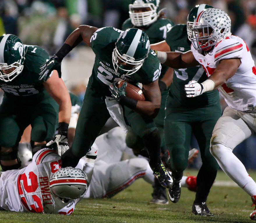 . Ohio State\'s Tyvis Powell (23) and Joshua Perry, right, stop Michigan State\'s Delton Williams, center, during the second quarter of an NCAA college football game, Saturday, Nov. 8, 2014, in East Lansing, Mich. (AP Photo/Al Goldis)
