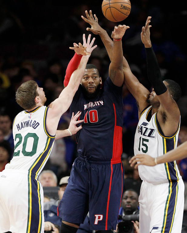 . Detroit Pistons\' Greg Monroe (10) is forced to pass the ball away from Utah Jazz\'s Gordon Hayward (20) and Derrick Favors (15) during the first half of an NBA basketball game Sunday, Nov. 9, 2014, in Auburn Hills, Mich.  (AP Photo/Duane Burleson)