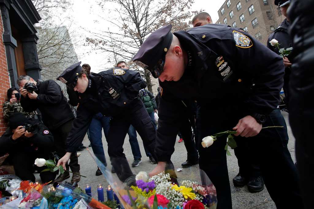 """. New York City police officer Darren Cox, right, accompanied by fellow officers, leaves flowers at a memorial in the Bedford Stuyvesant neighborhood of the Brooklyn borough of New York, Sunday, Dec. 21, 2014 in honor of two police officers who were shot there Saturday. Ismaaiyl Brinsley, who vowed online to shoot two \""""pigs\"""" in retaliation for the police chokehold death of Eric Garner, ambushed two New York City officers in a patrol car Saturday and fatally shot them in broad daylight before running to a subway station and killing himself, authorities said. (AP Photo/Mark Lennihan)"""