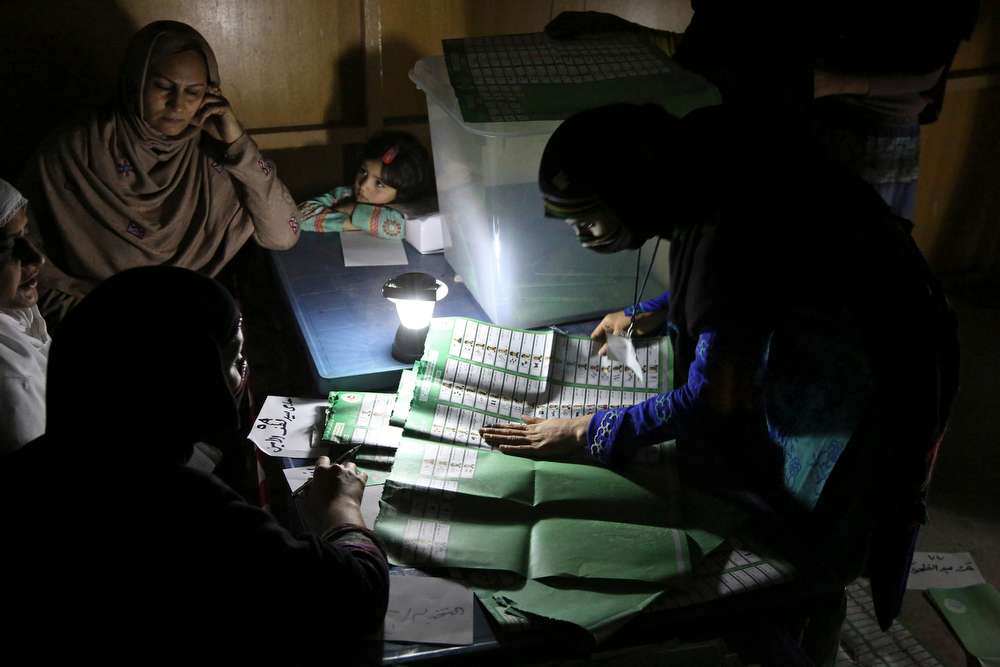 . Afghan election workers count ballots by the light of a lantern at a polling station in Jalalabad, east of Kabul, Afghanistan, Saturday, April 5, 2014. Across Afghanistan, voters turned out in droves Saturday to cast ballots in a crucial presidential election. The vote will decide who will replace President Hamid Karzai, who is barred constitutionally from seeking a third term. Partial results are expected as soon as Sunday. (AP Photo/Rahmat Gul)