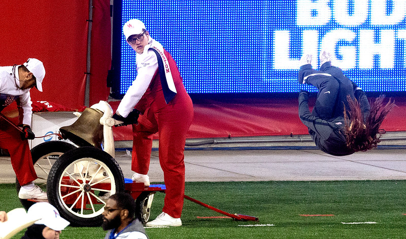 A Victory Bell ringer is distracted by an inverted cheerleader.