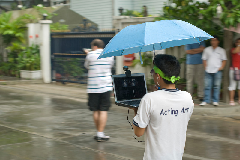Man carrying laptop and umbrella during the protests