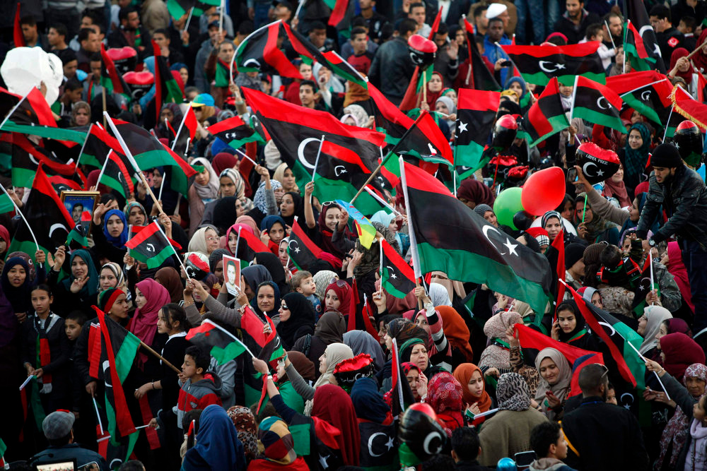 . People wave Libyan flags during celebrations commemorating the second anniversary of the country\'s February 17 revolution, at Martyrs\' Square in Tripoli February 17, 2013. REUTERS/Ismail Zitouny
