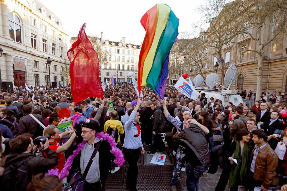 """. People gather to celebrate the passage of a law allowing same-sex couple to marry and adopt children, in Paris April 23, 2013. French lawmakers passed a bill on Tuesday, a flagship reform pledge by French President which sparked often violent street protests and a rise in homophobic attacks. The law legalizes gay marriage and gives gay and lesbian couples adoption rights. Sign reads, \""""Yes to Equality\"""".   REUTERS/Charles Platiau"""