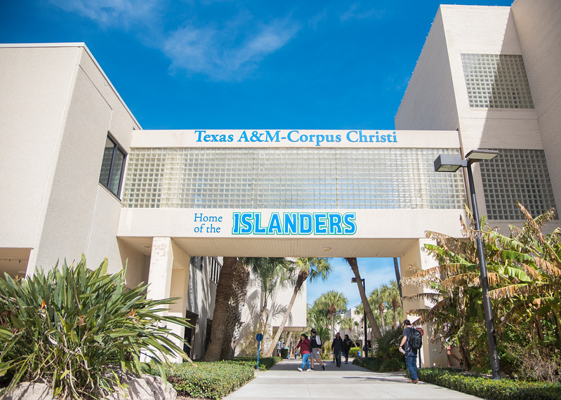 """Students walk between the Center for Instruction and Center for Science under the new """"Home of the Islanders"""" sign."""