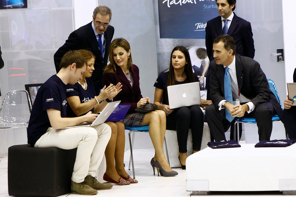 . The Prince of Spain, Felipe de Borbon (1R) and his wife Leticia Ortiz (3L) sit with youths during their visit to the Telefonica Stand at the Mobile World Congress in Barcelona, on February 24, 2014.  The Mobile World Congress runs from the 24 to 27 February where participants and visitors alike can attend conferences, network, discover cutting-edge products and technologies at among the 1,700 exhibitors as well as seek industry opportunities and make deals.   QUIQUE GARCIA/AFP/Getty Images