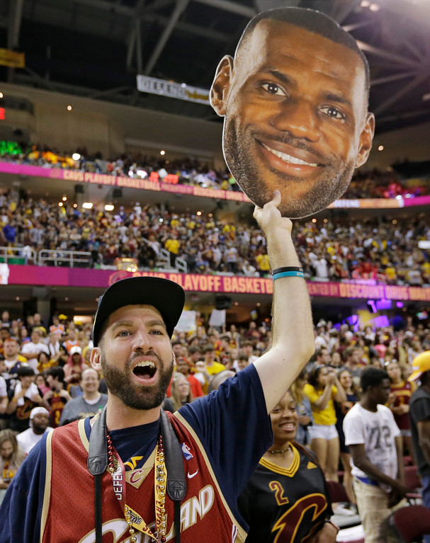 . Richard Marous holds up a cutout of Lebron James as he cheers during a watch party at Quicken Loans Arena during Game 5 of basketball\'s NBA Finals between the Golden State Warriors and the Cleveland Cavaliers, Monday, June 12, 2017, in Cleveland. (AP Photo/Tony Dejak)