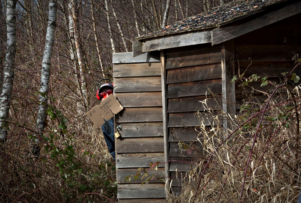 . A member of the Vancouver Gun Club peeks out from behind the hut where sporting clays are fired from at the club\'s facility in Richmond, British Columbia February 17, 2013. Formed in 1924 the Vancouver Gun Club, which is a shotgun-only club, has a regular membership of about 400 and sells an estimated 1100 day passes each year. Canada has very strict laws controlling the use of handguns and violent crime is relatively rare. Picture taken February 17, 2013. REUTERS/Andy Clark
