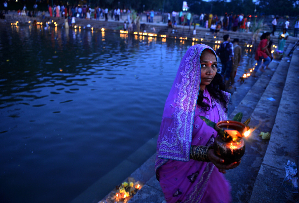 . Hindu devotees pray to the Sun God as part of the Chhath puja at a lake in Bangalore on November 8, 2013. The Chhath puja includes holy bathing, fasting and abstaining from drinking water (Vratta), standing in water for long periods of time, and offering prashad (prayer offerings) and arghya to the setting and rising sun. AFP PHOTO/Manjunath Kiran/AFP/Getty Images