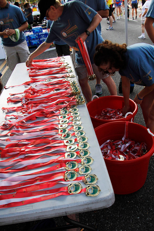 . Organizers prepare the 5k medals for the participants, during the 5th Annual Pasadena Marathon Event, at Pasadena City College, in Pasadena, Sunday, June 30, 2013. (SXCITY/Correspondent Photo by James Carbone)