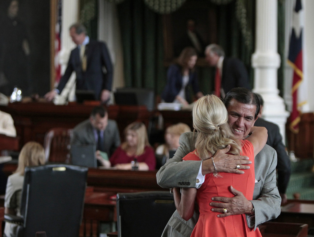 . Texas Sen. Wendy Davis (D-Ft. Worth) is hugged by Texas Sen. Eddie Lucio (D-Brownsville) on the Texas Senate floor on the first day of the second legislative special session on July 1, 2013 in Austin, Texas. This is the first day of a second legislative special session called by Texas Gov. Rick Perry to pass a restrictive abortion law through the Texas legislature. The first attempt was defeated after opponents of the law were able to stall the vote until after first special session had ended.  (Photo by Erich Schlegel/Getty Images)