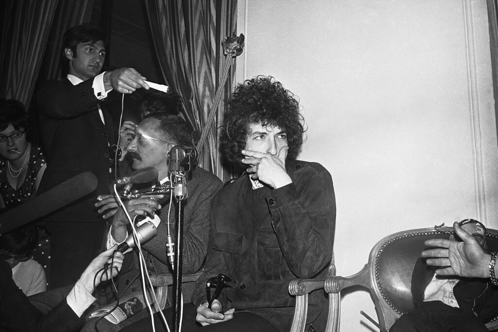 . American folk singer Bob Dylan covers his mouth as he faces the media during a press conference at the Hotel George V in Paris, France on May 23, 1966. He will appear on Tuesday at the Paris Olympia music-hall. Beside him is a puppet. (AP Photo/Pierre Godot)