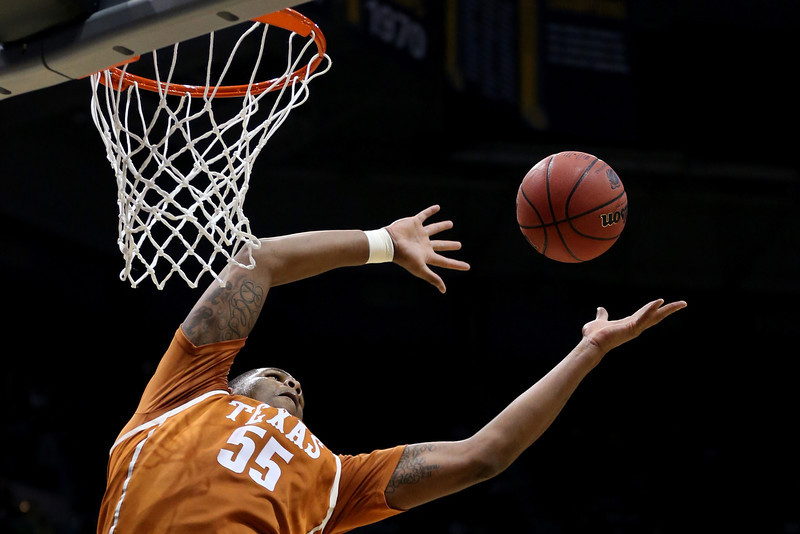 . Cameron Ridley #55 of the Texas Longhorns rebounds the ball against the Michigan Wolverines  during the third round of the 2014 NCAA Men\'s Basketball Tournament at BMO Harris Bradley Center on March 22, 2014 in Milwaukee, Wisconsin.  (Photo by Jonathan Daniel/Getty Images)