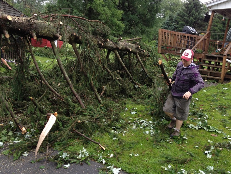 . Josh Herter drags branches as they are cut as he and others clean up at his Grandmothers home on West Main Street and Station Street in Verona following an early morning storm on Wednesday, June 18, 2014. JOHN HAEGER @ONEIDAPHOTO ON TWITTER/ONEIDA DAILY DISPATCH