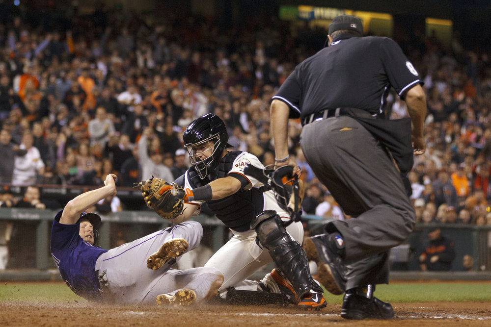 . DJ LeMahieu #9 of the Colorado Rockies is tagged out by Andrew Susac #34 of the San Francisco Giants at home plate in front of umpire Doug Eddings #88 during the seventh inning at AT&T Park on August 25, 2014 in San Francisco, California.  (Photo by Jason O. Watson/Getty Images)