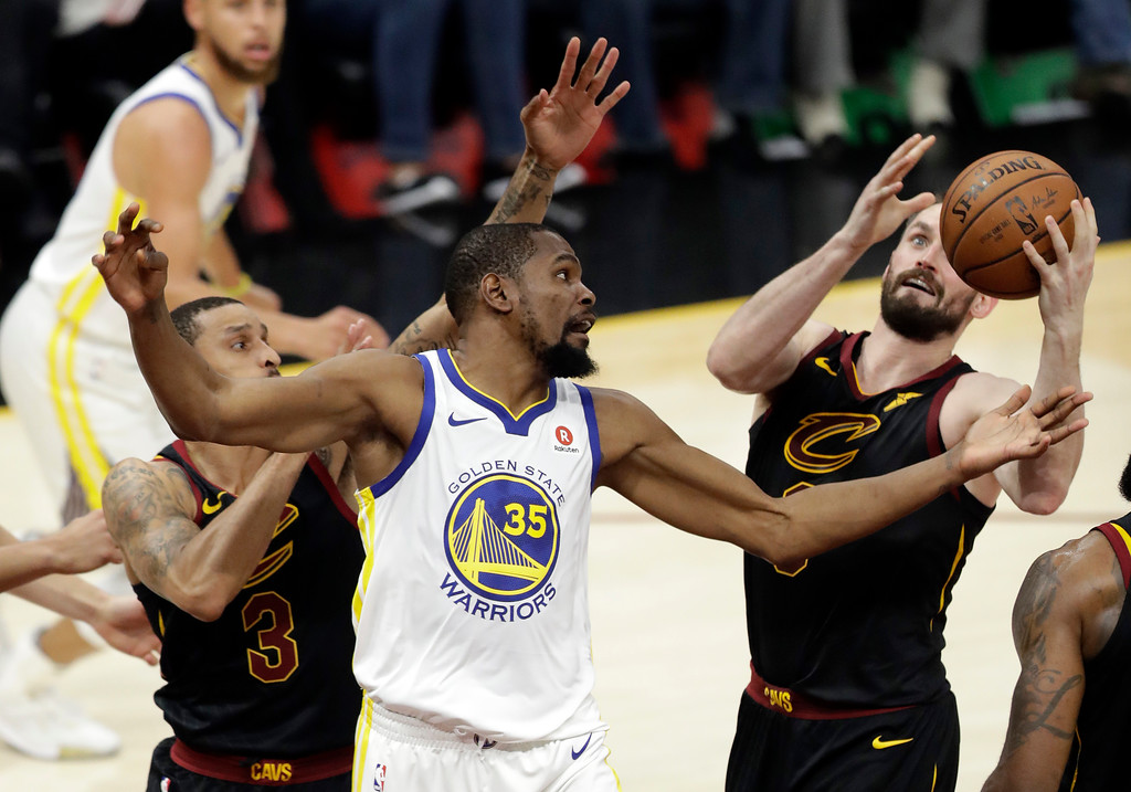 . Golden State Warriors\' Kevin Durant (35) and Cleveland Cavaliers\' Kevin Love, right, vie for a loose ball during the first half of Game 3 of basketball\'s NBA Finals, Wednesday, June 6, 2018, in Cleveland. (AP Photo/Tony Dejak)