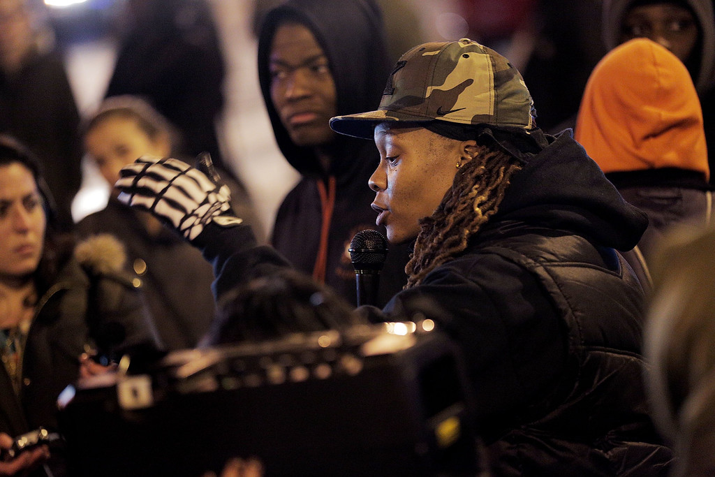 . Essence Coggins, of Oxon Hill, Maryland, speaks as demonstrators block an intersection in the Adams Morgan neighborhood during a protest against a New York grand jury decision December 3, 2014 in Washington, DC. The grand jury decided not to indict police officer Daniel Pantaleo in the death of an unarmed black man, Eric Garner, after putting him in a chokehold.  (Photo by T.J. Kirkpatrick/Getty Images)