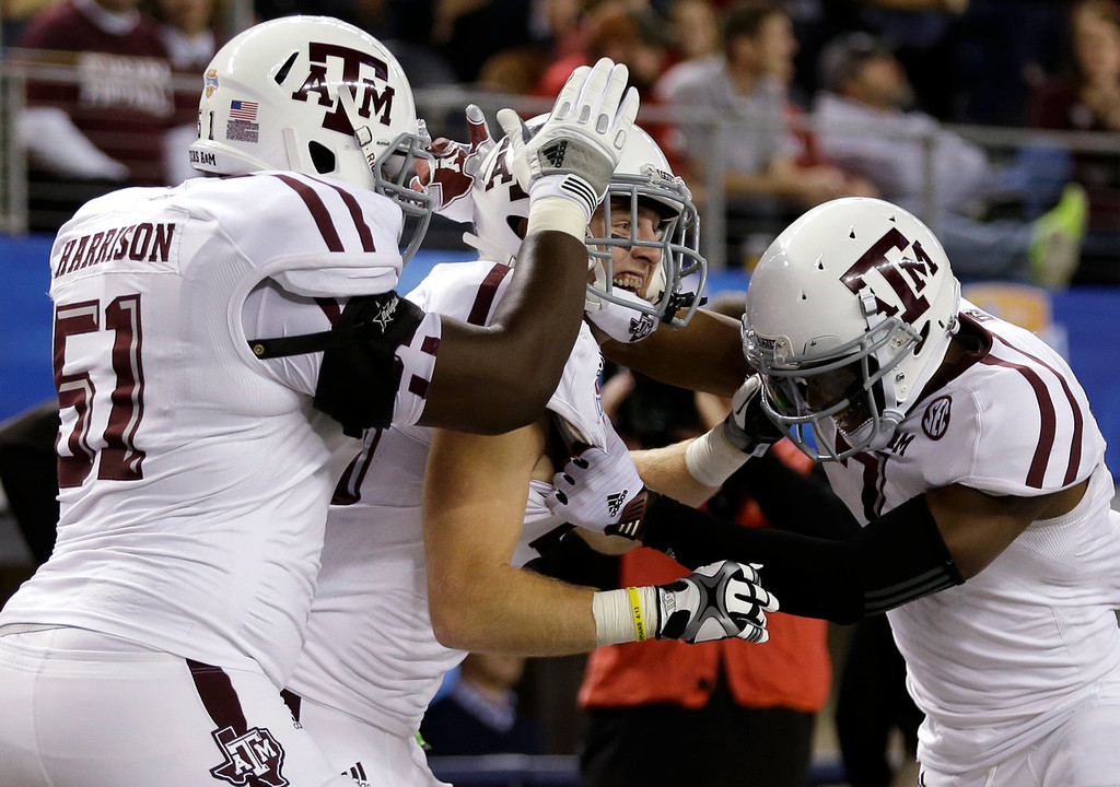 . Texas A&M\'s Jarvis Harrison (51) and Uzoma Nwachukwu, right, celebrate with Ryan Swope, center, following his touchdown in the second half of the Cotton Bowl NCAA college football game against Oklahoma on Friday, Jan. 4, 2013, in Arlington, Texas. (AP Photo/LM Otero)