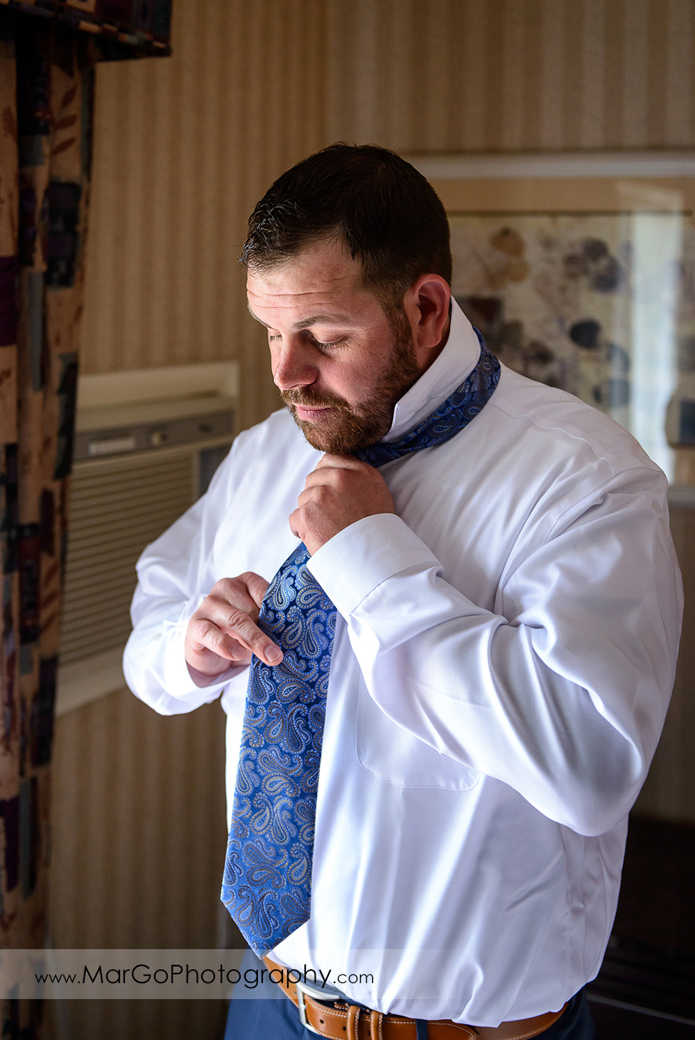 groom fixing tie during wedding preparation at Los Gatos Lodge