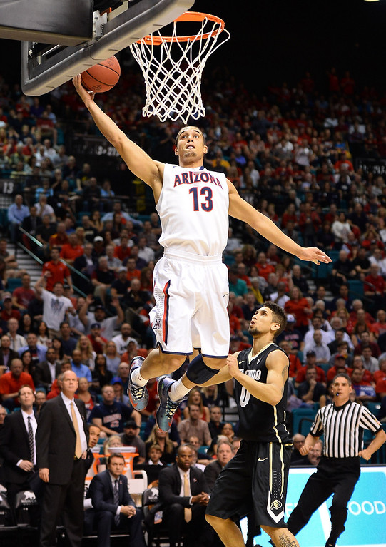 . LAS VEGAS, NV - MARCH 14:  Nick Johnson #13 of the Arizona Wildcats dunks off an alley-oop pass against Askia Booker #0 of the Colorado Buffaloes during a semifinal game of the Pac-12 Basketball Tournament at the MGM Grand Garden Arena on March 14, 2014 in Las Vegas, Nevada.  (Photo by Ethan Miller/Getty Images)