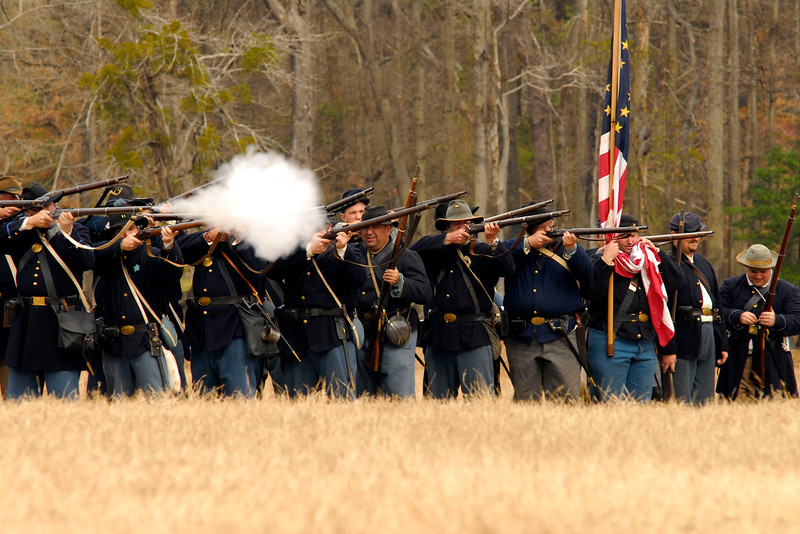 Union infantry reenactors hold their line while firing across the battlefield. The Skirmish at Gamble's Hotel happened on March 5, 1885 when 500 federal soldiers, under the command of Reuben Williams of the 12th Indiana Infantry, marched into Florence to destroy the railroad depot but were met by Confederate soldiers backed up with 400 militia. The reenactment, held by the 23rd South Carolina Infantry, was held at the Rankin Plantation in Florence, South Carolina on Saturday, March 5, 2011. Photo Copyright 2011 Jason Barnette