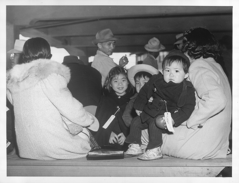 """""""A far cry from Tanforan as Bay Area horse racing fans knew it in pre-war times is this scene at the peninsula track today as vanguard of SF Japs, including children arrived there.""""--caption on photograph"""
