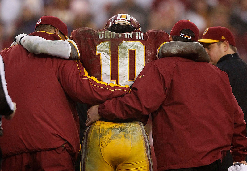 . Washington Redskins starting quarterback Robert Griffin III (C) is helped off the field by team trainers late in the fourth quarter with an injury against the Baltimore Ravens during their NFL football game in Landover, Maryland December 9, 2012.     REUTERS/Gary Cameron   (UNITED STATES - Tags: SPORT FOOTBALL TPX IMAGES OF THE DAY)