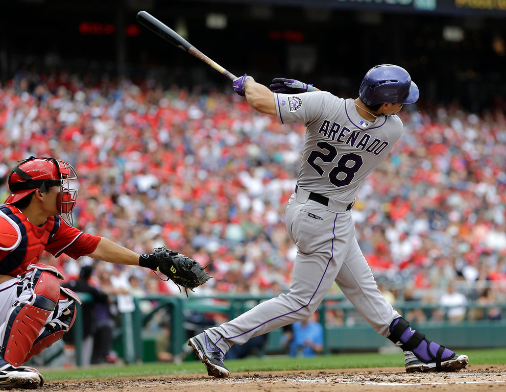 . Colorado Rockies\' Nolan Arenado (28) hits a solo home run as Washington Nationals catcher Kurt Suzuki looks on in the fourth inning of a baseball game at Nationals Park, Sunday, June 23, 2013, in Washington. (AP Photo/Carolyn Kaster)