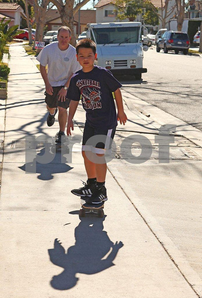 Dad teaching son how to ride a skateboard.