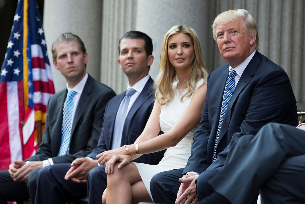 . Donald Trump, right, sits with, from left, Eric Trump, Donald Trump Jr., and Ivanka Trump during a ground breaking ceremony for the Trump International Hotel on the site of the Old Post Office, on Wednesday, July 23, 2014, in Washington. (AP Photo)