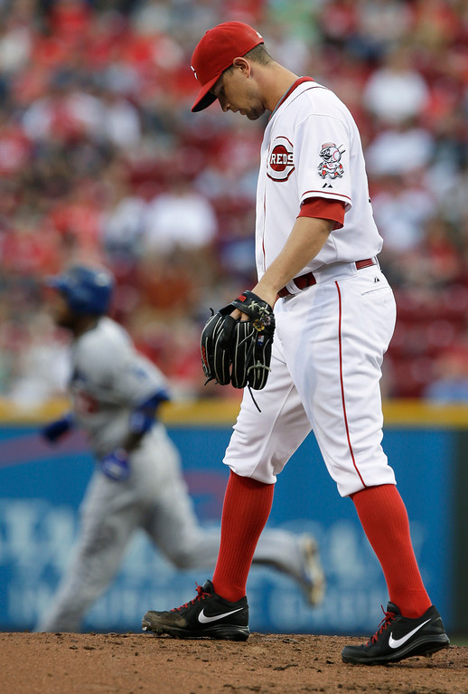. Cincinnati Reds starting pitcher Mike Leake stands on the mound after giving up a two-run home run to Los Angeles Dodgers\' Hanley Ramirez, rounding the bases at left, in the first inning of a baseball game, Friday, Sept. 6, 2013, in Cincinnati. (AP Photo/Al Behrman)