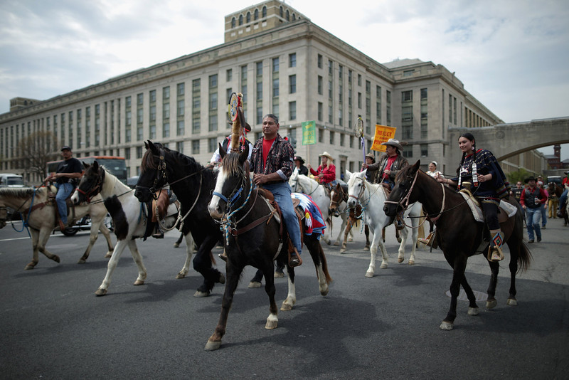 ". Members of the Cowboy and Indian Alliance, including Native Americans, farmers and ranchers from across the United States, ride horseback down Independence Avenue as part of a demonstration against the proposed Keystone XL pipeline April 22, 2014 in Washington, DC. As part of its ""Reject and Protect\"" protest, the Cowboy and Indian Alliance is organizing a weeklong series of actions by farmers, ranchers and tribes to show their opposition to the pipeline.  (Photo by Chip Somodevilla/Getty Images)"