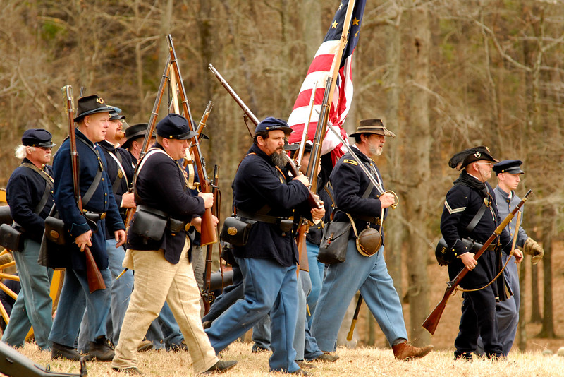 After taking the artillery on the hill, reenactors with the 12th Indiana Infantry march across the battlefield. The Skirmish at Gamble's Hotel happened on March 5, 1885 when 500 federal soldiers, under the command of Reuben Williams of the 12th Indiana Infantry, marched into Florence to destroy the railroad depot but were met by Confederate soldiers backed up with 400 militia. The reenactment, held by the 23rd South Carolina Infantry, was held at the Rankin Plantation in Florence, South Carolina on Saturday, March 5, 2011. Photo Copyright 2011 Jason Barnette