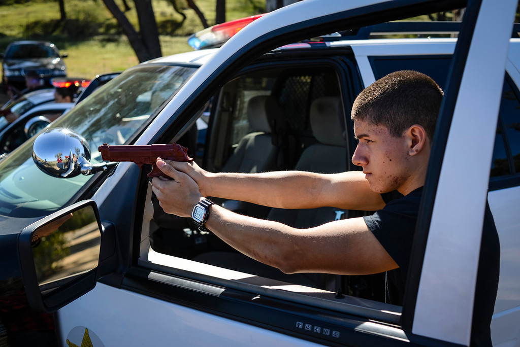 """. Edward martinez, 17, keeps his gun trained on a car during a felony stop re-enactment at Pitches Detention Center Sunday.  Law enforcement explorer posts participated in a weekend-long competition to sharpen their skills.  During team events such as \""""prowler\"""", \""""felony stop\"""", \""""active shooter\"""" and \""""mud Race\"""", explorers were graded on their skills in each of the tests.  Photo by David Crane/Staff Photographer"""