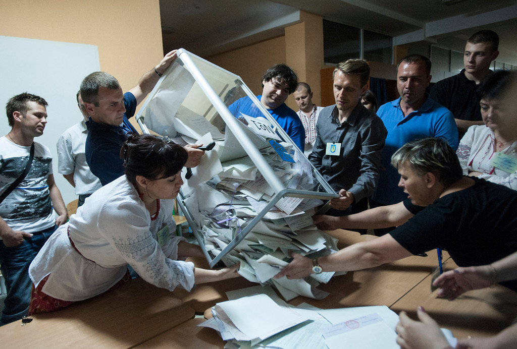 . Election commission officials count ballots at a polling station in Kiev, Ukraine, on Sunday, May 25, 2014. Ukraine\'s critical presidential election went underway Sunday under the wary scrutiny of a world eager for stability in a country. An exit poll showed that billionaire candy-maker Petro Poroshenko won election in the first round. (AP Photo/Evgeniy Maloletka)