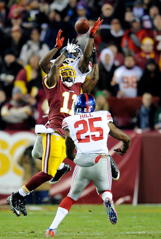 . Washington Redskins wide receiver Aldrick Robinson (11) can\'t make the catch as he is covered by New York Giants cornerback Prince Amukamara, behind, and free safety Will Hill, during the first half of an NFL football game Sunday, Dec. 1, 2013, in Landover, Md. (AP Photo/Nick Wass)
