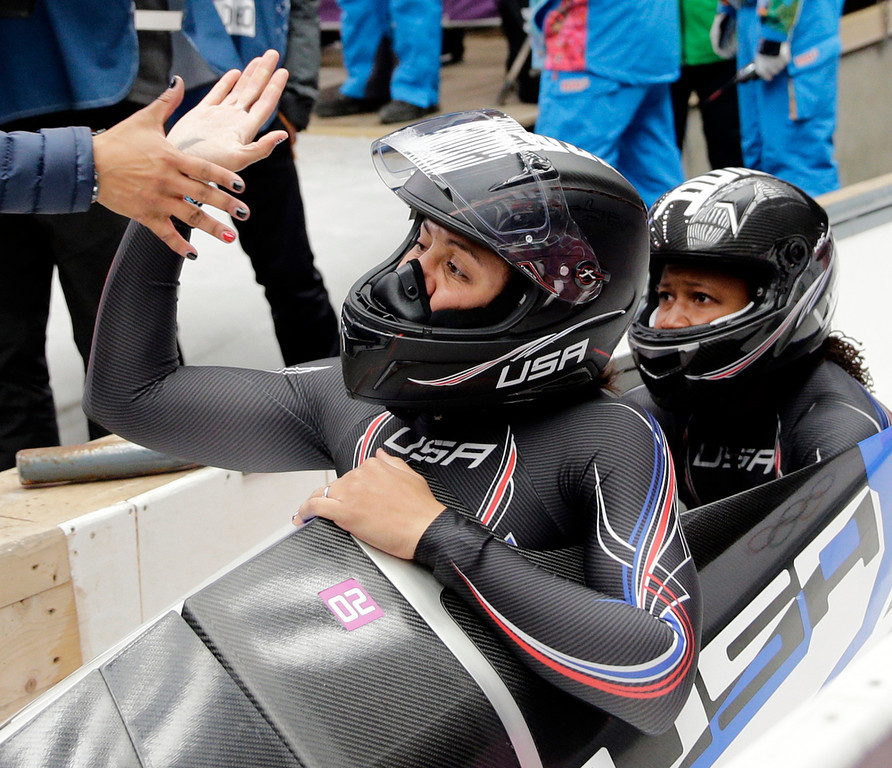 . The team from the United States USA-1, piloted by Elana Meyers with brakeman Lauryn Williams, get congratulated in the finish area after their silver medal run during the women\'s bobsled competition at the 2014 Winter Olympics, Wednesday, Feb. 19, 2014, in Krasnaya Polyana, Russia. (AP Photo/Jae C. Hong)