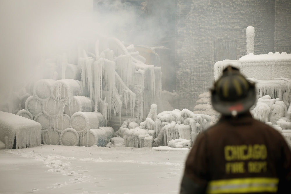 . Firefighters help to extinguish a massive blaze at a vacant warehouse on January 23, 2013 in Chicago, Illinois. More than 200 firefighters battled a five-alarm fire as temperatures were in the single digits. (Photo by Scott Olson/Getty Images)