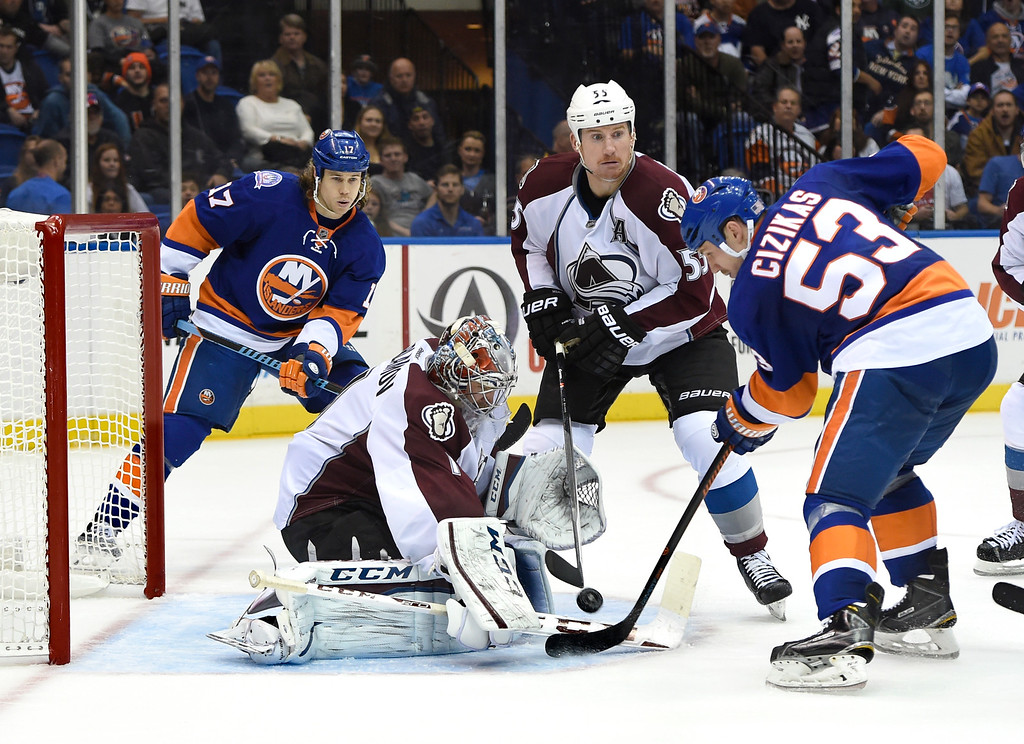 . Colorado Avalanche goalie Semyon Varlamov (1) blocks a shot on goal by New York Islanders center Casey Cizikas (53) as Islanders left wing Matt Martin (17) and  Avalanche\'s left wing Cody McLeod (55) look on in the second period of an NHL hockey game at Nassau Coliseum on Tuesday, Nov. 11, 2014, in Uniondale, N.Y. (AP Photo/Kathy Kmonicek)