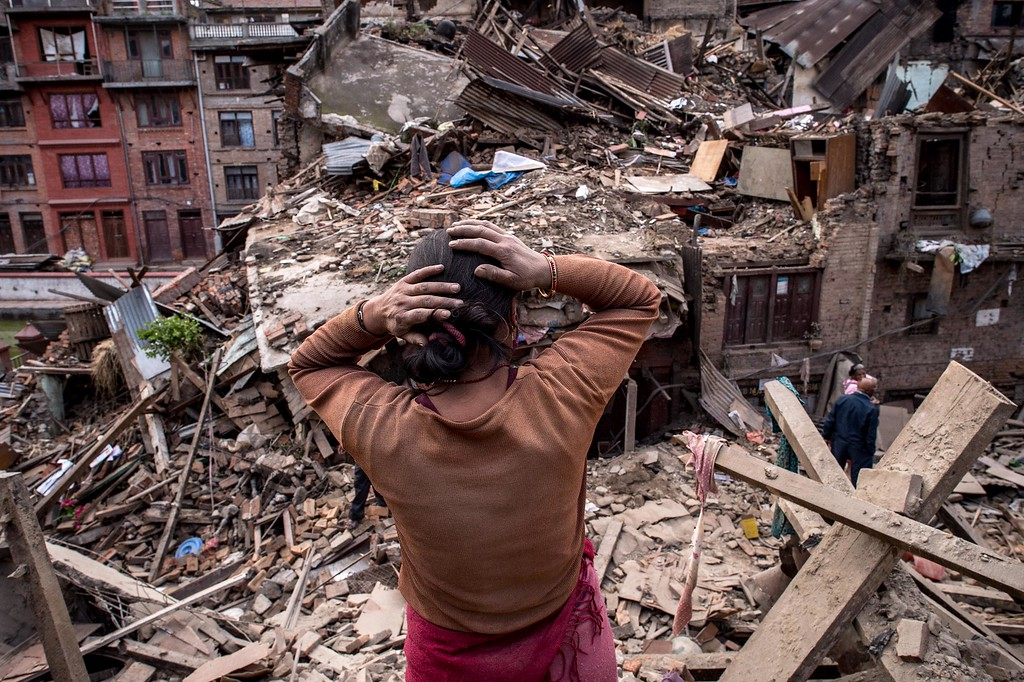 . A Nepalese earthquake victims looks on among debris of collapsed buildings on April 29, 2015 in Bhaktapur, Nepal. A major 7.8 earthquake hit Kathmandu mid-day on Saturday, and was followed by multiple aftershocks that triggered avalanches on Mt. Everest that buried mountain climbers in their base camps. Many houses, buildings and temples in the capital were destroyed during the earthquake, leaving over 5000 dead and many more trapped under the debris, as emergency rescue workers attempt to clear debris and find survivors. Regular aftershocks have hampered recovery missions as locals, officials and aid workers attempt to recover bodies from the rubble.  (Photo by David Ramos/Getty Images)