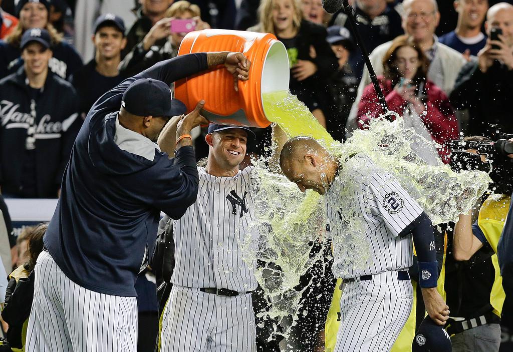 . New York Yankees\' C.C. Sabathia, left, and Brett Gardner douse Derek Jeter after Jeter drove in the winning run against the Baltimore Orioles in the ninth inning of a baseball game, Thursday, Sept. 25, 2014, in New York. The Yankees won 6-5 in Jeter\'s last home game. (AP Photo/Julie Jacobson)