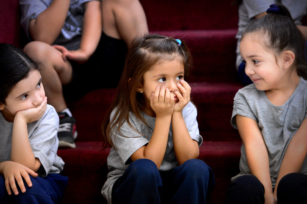 . From left, Kindergarteners Emily Brieno, Maegan Cericos, and Audrina Castro, all 5, watch Chinese students from Harbin Normal University as they visit Immaculate Conception Catholic School in Monrovia Wednesday, January 22, 2014. (Photo by Sarah Reingewirtz/Pasadena Star-News)