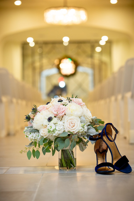 vase of blush roses next to wedding heals sitting in the aisle