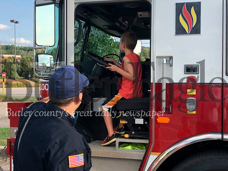 Tyler Palascak, 7, of Cranberry Township, sits at the helm of an Adams Area Fire District truck as firefighter Andrew Blaney looks on Tuedsay during the National Night Out celebration.
