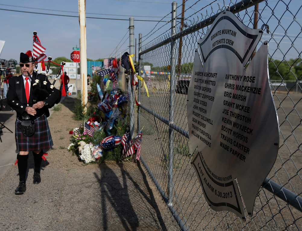 . Don Manafield pays his respects by playing a bagpipe at a makeshift memorial outside the Granite Mountain Interagency Hotshot Crew fire station, Tuesday, July 2, 2013, in Prescott, Ariz., honoring 19 firefighters killed battling a wildfire near Yarnell, Ariz., Sunday.  (AP Photo/Chris Carlson)