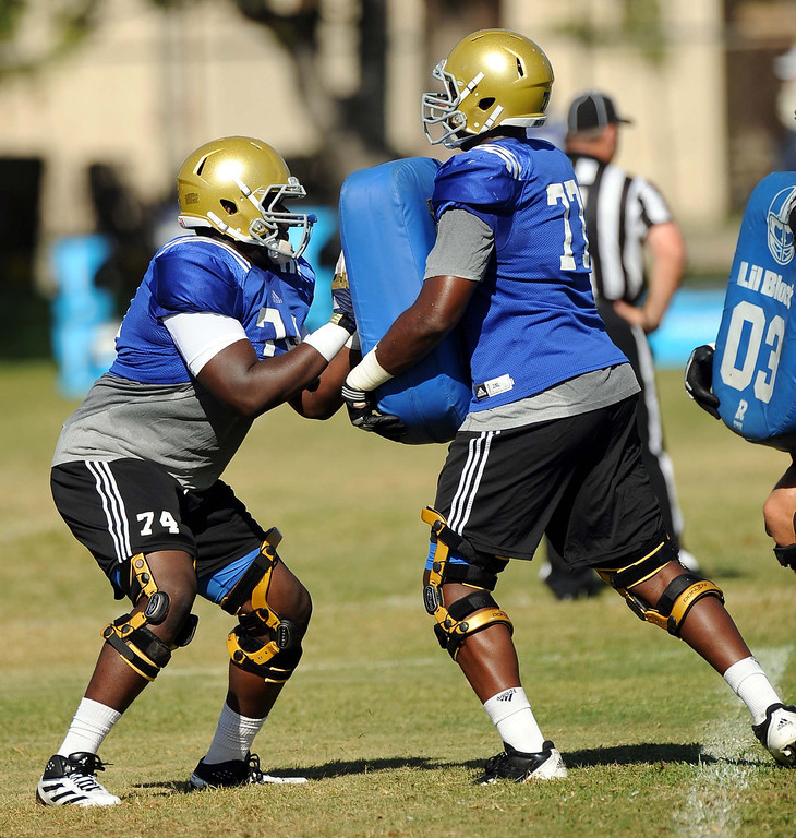 . Offense guard #74 Caleb Benenoch, and #77 Torian White works out a play during UCLA football practice held at California State University San Bernardino August 14, 2013.LaFonzo Carter/ Staff Photographer