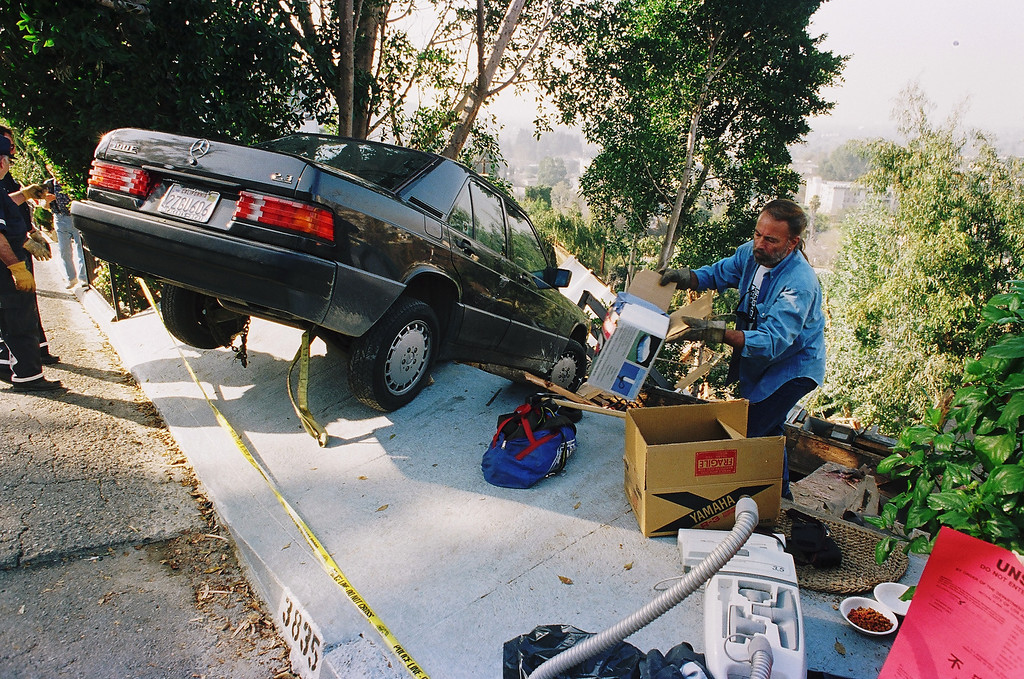 . A friend retrieves belongings for the owner of a hillside home on Buena Park Drive in Studio City.  The home was destroyed.   Los Angeles Daily News file photo