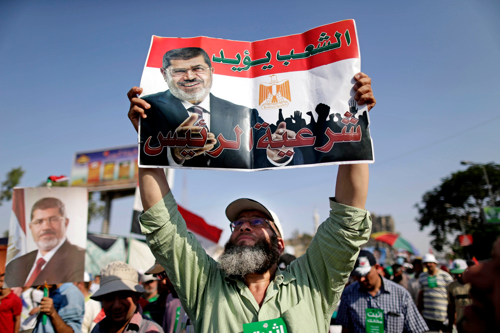 ". A supporter of Egypt\'s Islamist President Mohammed Morsi holds a poster with Arabic that reads, ""the people support legitimacy for the president,\"" during a rally, in Nasser City, Cairo, Egypt, Wednesday, July 3, 2013. The deadline on the military\'s ultimatum to President Mohammed Morsi has expired, with 48 hours passing since the time it was issued. Giant cheering crowds of Morsi\'s opponents have been gathered in Cairo\'s Tahrir Square and other locations nationwide, waving flags furiously in expection that the military will act to remove the Islamist president after the deadline ends.  (AP Photo/Hassan Ammar)"